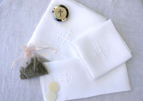 three church linens placed with lavender sachet and communion wafers